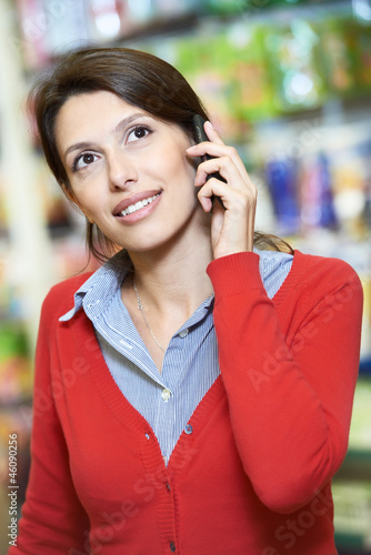 Young woman speaking on phone in shop