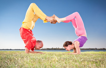 Yoga couple, man and woman doing Vrschikasana scorpion pose