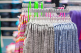 Color sweaters of blue and grey on stands in kids mall