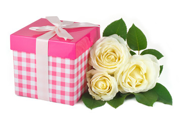 Gift box with a bow and a bouquet of delicate roses