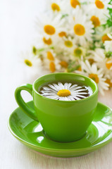 Herbal chamomile tea in a green cup
