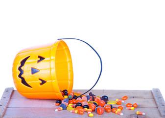 Halloween candy and pumpkin bucket on wood