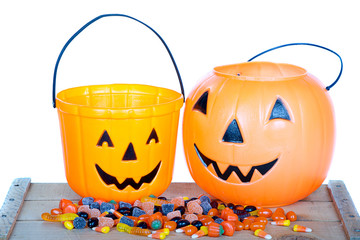 Halloween candy and pumpkin bucket on wood