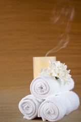 White towels, flower and blown-out candle on brown bamboo mat.