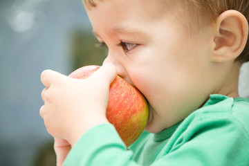 Little child is biting red apple and smile
