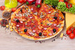 delicious pizza and vegetables on wooden table