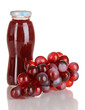 Delicious grapes juice in glass bottle and pink grapes next to