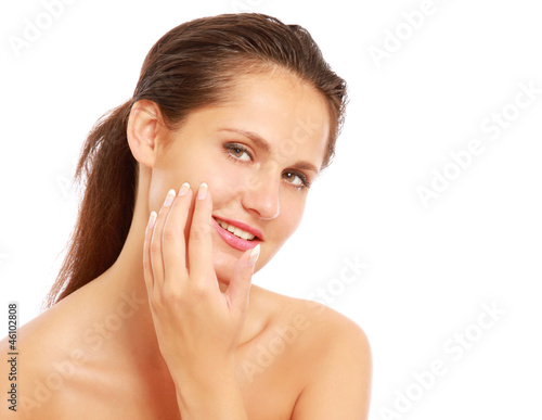 A beautiful woman is applying cream on her face over white