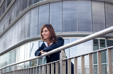 Lächelnde Frau steht am Geländer