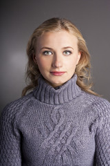 Portrait of a blonde in a sweater. studio