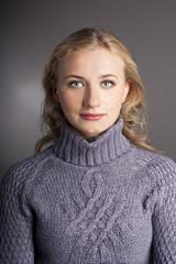 Portrait of a blonde in a sweater. studio