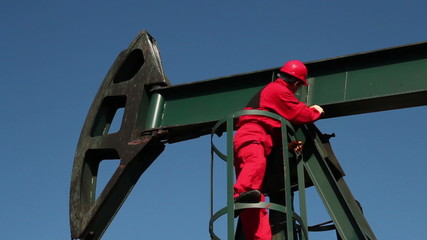 Worker in Action at Pump Jack Oil Well
