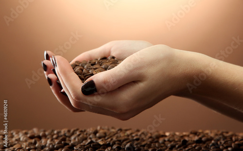 female hands with coffee beans, on brown background