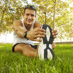 sport man stretching at the park - fitness concepts