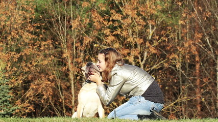teen girl playing with dog in autumnal park
