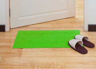 Green doormat with house slippers