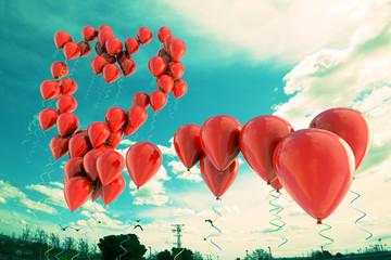 globos rojos formando una forma de corazón en el cielo