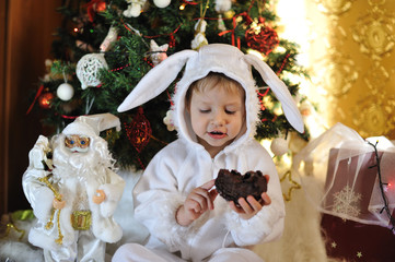 Node Christmas tree sits a boy dressed as a white rabbit
