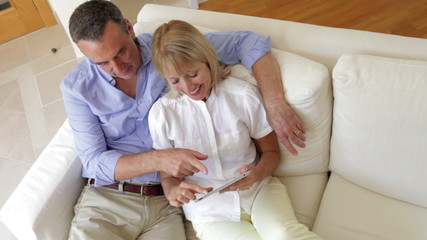 Senior Couple Sitting On Sofa Using Digital Tablet