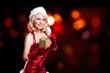 Weihnachtsfrau im roten Minikleid mit Geschenk