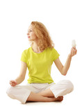A woman with an energy-saving bulb meditating, isolated on white