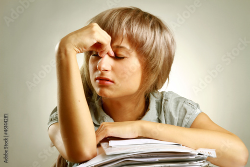 A tired young woman sitting at the desk