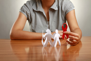 Female hands holding paper people and a red