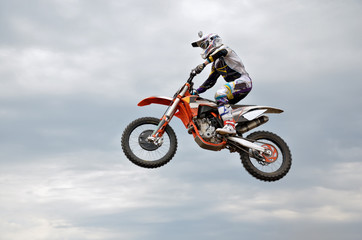 motocross rider jumps high against the sky