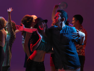 girl and guy dancing and smiling at party