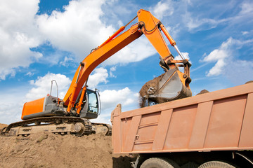Backhoe loading soil or sand into dump truck body