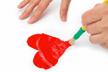 Female hand with brush paint draws the heart.