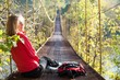 Woman hiking sitting in suspension bridge and resting