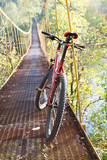 Red bike standing in suspension bridge
