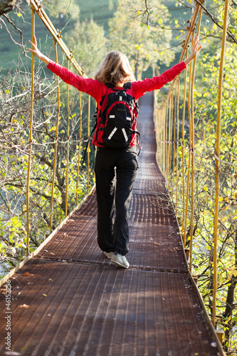 Woman hiking in suspension bridge with outstretched to hands