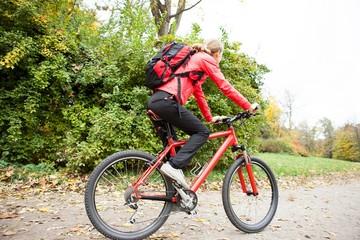 Woman cyclist riding a bike in autumn park