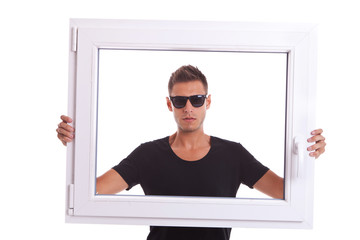 man wearing sunglasses is holding a pvc window frame