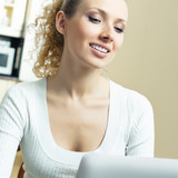 Cheerful woman with laptop, at home