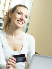 Cheerful woman paying by plastic card