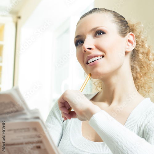 Young happy woman with newspaper at home