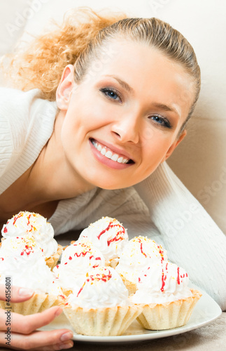 Cheerful smiling woman with plate of cakes