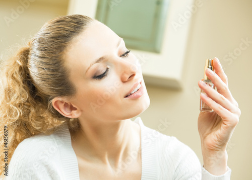 Cheerful woman with perfum bottle