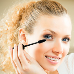 Cheerful woman applying mascara with lash brush