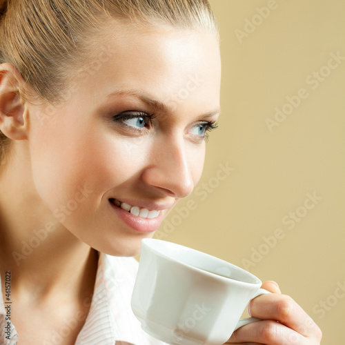 Young woman drinking coffee or tea, at home