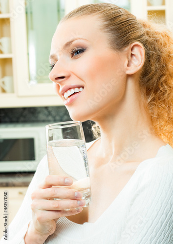 Cheerful woman with glass of water at home
