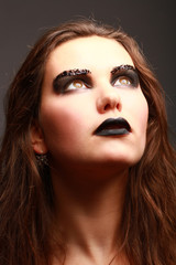 Close up fashion portrait of woman with black make up looking up