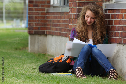 GIrl sit in a grass and study