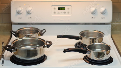Four pots full of boiling water on the stove. Accelerated motion