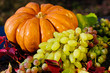 Harvested pumpkins with grapes and fall leaves