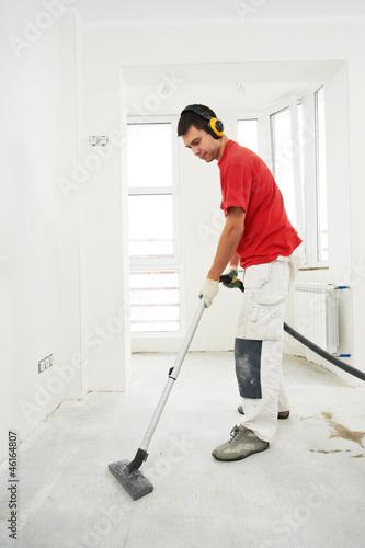 Leinwanddruck Bild worker cleaning floor at home renovation