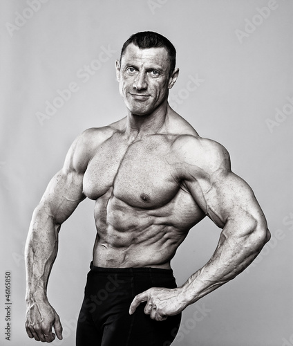 Portrait of handsome bodybuilder posing on white background